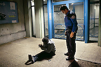 Switzerland. Geneva. Paquis neighborhood. A police officer asks a drunken black man seated on the ground  to stand up and return at home. The african man from Guinea is under the influence of alcohol. The policeman is wearing a ballistic vest, bulletproof vest or bullet-resistant vest which is an item of personal armor that helps absorb the impact from knives, firearm-fired projectiles and shrapnel from explosions, and is worn on the torso. Soft vests are made from many layers of woven or laminated fibers and can be capable of protecting the wearer from small-caliber handgun and shotgun projectiles. 25.03.12 © 2012 Didier Ruef