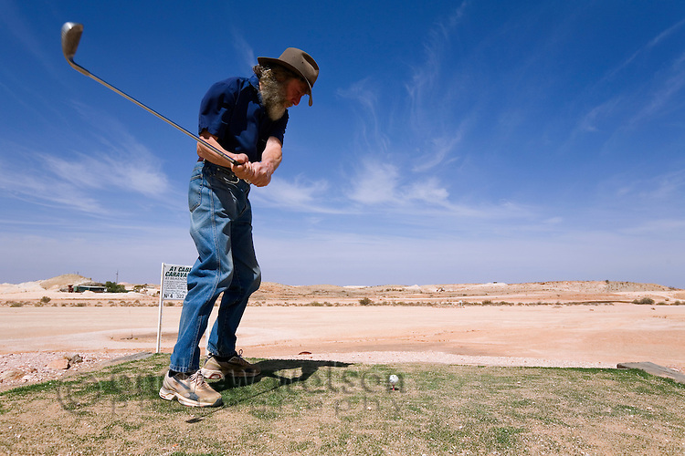 Teeing off at the Coober Pedy Opal Fields Golf Club.  The unique desert course is completely grassless with fairways of bare earth and putting greens made from oiled sand.  Coober Pedy, South Australia, AUSTRALIA