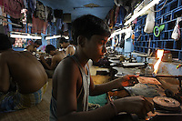 Young boys work as artisanal gold smiths in Kolkata (Calcutta)....These guys make about 3-400 USD a month at the top end.  They live in the workplace... the clothes you see hanging above them are their clothes, their closet as it were.  At night they move the worktables aside and sleep on the floor.