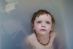 Close up of a young girls face in a bath wearing a necklace