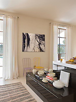 In the open-plan kitchen area a large black and white photograph is displayed better a pair of French windows that lead onto the terrace