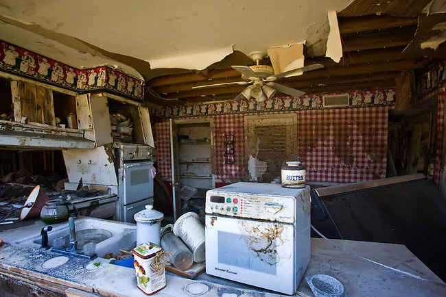 The kitchen of a home in the Lakeview area that suffered major damage due to Hurricane Katrina flooding in New Orleans, Louisiana. Many of these homes' interiors like this one remain untouched; floors are covered in flood debris and rubble while the walls and surfaces are still scab-covered layers of mold.