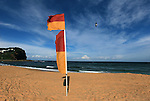 Life Saving flags fly in the late afternoon at Copacabana Beach on the Central Coast of New South Wales Photo: Steve Christo