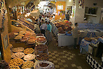 A bright market with shoppers greeting friends, Marakesh, Morocco.