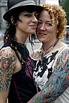 Half Lenth portrait of Punk Dyke Couple with tattoos at the Dyke Parade, dykes march down 5th Avenue to Washington Square Park the day before the Gay and Lesbian Pride Parade.  Lesbian dykes showing gender and sexual identity pride and orientation.