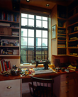 A well organised work table by a window overlooking the New York skyline is equipped with an old sewing machine