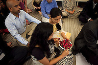 Flowers are passed around as staff and guests sit on the floor barefooted in respect of the puja (prayer and blessing) at the opening ceremony of the new Bill & Melinda Gates Foundation office in New Delhi, India on 17th December 2010. Photo by Suzanne Lee for Gates Foundation