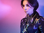 Beautiful woman wearing fashionable clothing and accessories in colorful purple blue light
