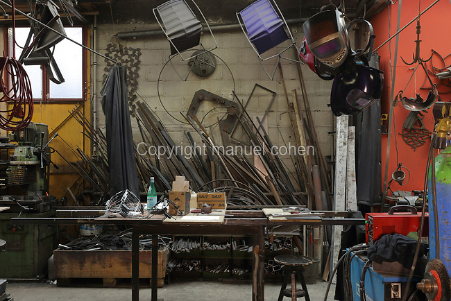 Workbench and raw materials in the Soleil Rouge workshop of Nicolas Desbons, metalworker and artist, photographed in 2017, in Montreuil, a suburb of Paris, France. Desbons works mainly in steel but often in conjunction with other materials such as fibreglass, glass and clay, using both cold metal and forge techniques. He produces both figurative and abstract sculptures as well as furniture and lighting. Picture by Manuel Cohen