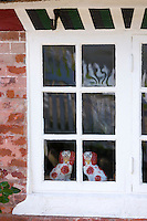Traditional Staffordshire dog figurines in window of cottage house on Fano Island - Fanoe - South Jutland, Denmark