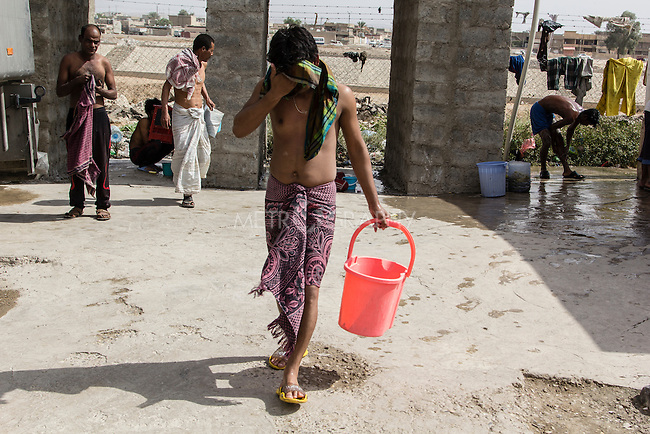 10/10/2014 -- Kirkuk, Iraq -- A Bangladeshi worker brings water to wash his clothes in the afternoon when the workers have two free hours they can spend in the garage where they live in.