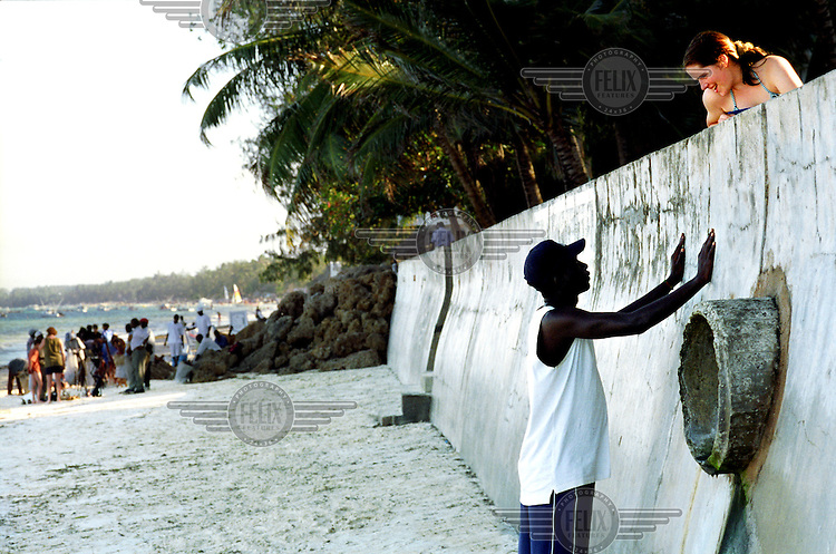 ©Sven Torfinn/Panos Pictures..Kenya, Mombasa, July 2002.on the beach, Kenyan man is chatting to young female tourist.the beaches around Mombasa are well known to tourists from Europe, not only for their ordinary touristic aspects (sand, sun, sea ...) but also to pick up / encounter local boyfriends / girlfriends, sometimes for one night, sometimes for money and sometimes in the hope to make it to Europe one day