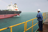 AL-BASRA OIL TERMINAL, IRAQ: A worker watches as an oil tanker waits to be towed into the Basra Oil Terminal..