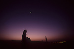 Woman enjoying the sunset in the desert outside Dubai, UAE>