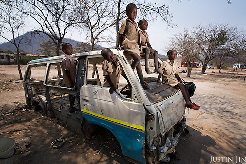 Children play in a destroyed van in drought-hit Masvingo Province, Zimbabwe, carry water to wash clothes. <br /> <br /> Drought in southern Africa is devastating communities in Zimbabwe, leaving 4 million people urgently in need of food aid. The government declared a state of emergency,. <br /> <br /> Here in Masvingo Province, the country's hardest hit province, vegetation has wilted, livestock is dying, and people are at serious risk of famine. <br /> <br /> Pictures shot by Justin Jin