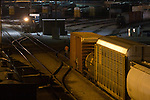 A switchman walks back to line a switch for his train to shove back into the yard as another yard job moves out with a cut of cars. This action is all happening after dark at Canadian Pacific's freight classification yard in Bensenville, IL.