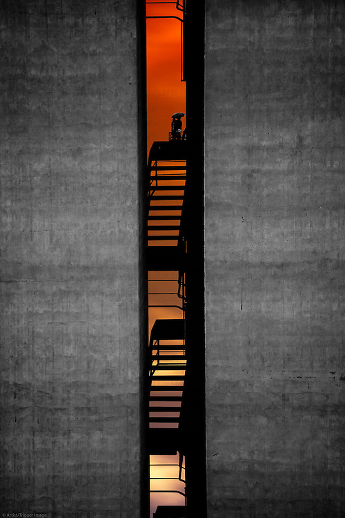 A staircase between two distinctive industrial buildings made of concrete and a pair, which looks into the sunset.