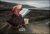 BNPS.co.uk (01202 558833)<br /> Pic: PhilYeomans/BNPS<br /> <br /> Rikey out on the Jurassic coast near Lyme Regis.<br /> <br /> kSquids in - Dorset artist can't keep up with demand - as her fossil art is done using incredibly scarce 200 million year-old fossilised ink.<br /> <br /> Rikey Austin, 49, extracts ink from a phragmoteuthid fossil, which are somewhere between a squid and a cuttlefish and lived approximately 200 million years ago. <br /> <br /> Her husband, geologist Paddy Howe, finds the fossils while walking along the Jurassic Coast in Lyme Regis, West Dorset, which is a hotbed of fossilised activity.<br /> <br /> Mrs Austin then powders the ink, adds a tiny bit of water and uses it to create captivating images of dinosaurs and other fossilised creatures. <br /> <br /> The phragmoteuthid defended itself by shooting out ink and some of the fossils still have their original pigment in an ink sack inside.<br /> <br /> However, these fossils do not preserve themselves as well as other fossils, so it is extremely rare to find one with its ink sack intact.<br /> <br /> As a result, the mother-of-three has only produced seven drawings since she first experimented with fossilised ink in 2010.