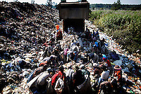 Illegal migrants from Myanmar gather as a truck unloads at a rubbish dump site near Mae Sot December 22, 2009. Despite terrible living condition and the fear from being send back to their country, several hundreds illegal migrants from Myanmar live and earn average one US dollar per day collecting plastic at the rubbish dump near the border town of Mae Sot. Myanmar's long standing political crisis has forced millions of people across the border for a better and safer life. The first refugees arrived and set up camps in the Myamar-Thailand border in 1984. Now there are over 140,000 refugees in nine official camps along Thailand's western border. Many more are expected to be in unofficial settlements.  REUTERS/Damir Sagolj (THAILAND)