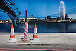 Cones and a hoarding showing the Thames River, Millennium Bridge and Tate Modern.