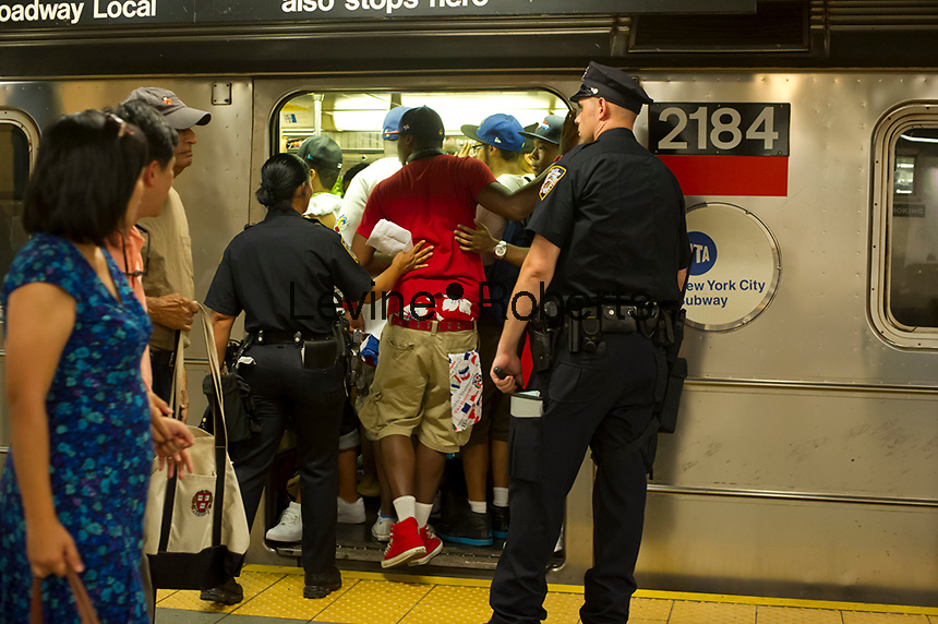 Revelers crowd the Number One subway train at the Columbus Circle station, traveling up to Washington Heights, after the Dominican Day parade in New York on Sunday, August 12, 2012. (© Frances M. Roberts)
