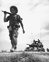 A French Foreign Legionnaire goes to war along the dry rib of a rice paddy, during a recent sweep through communist-held areas in the Red River Delta, between Haiphong and Hanoi.  Behind the Legionnaire is a U.S. gifted tank.  Ca.  1954.  Pix.  (USIA)<br /> EXACT DATE SHOT UNKNOWN<br /> NARA FILE #:  306-PS-54-10014<br /> WAR &amp; CONFLICT BOOK #:  382