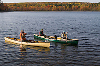 Canoeists paddle Harlow Lake with fall color near Marquette Michigan.