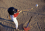 Young girl (7 years old) swinging bat at ball on T, concentrating on her swing, overhead view, Woodinville, Washington USA  MR
