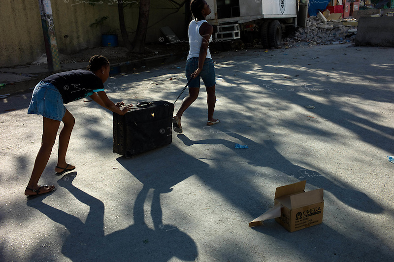 Port Au Prince, Haiti, Jan 17 2010.A couple of girl have salvaged some of their clothes from their destroyed house and carry them away.