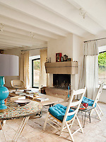 A turquoise lamp base and seat cushions add splashes of colour to the living room that has an otherwise pale palette of natural and white tones
