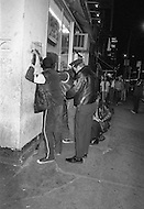 Manhattan, New York City, NY - May, 1980. NYPD police officers keep a watchful eye and batons at the ready while on patrol in Times Square. The area, once a cultural hub, full of theaters, music halls and upscale hotels, declined into a world of sex, drugs and crime and sleazy businesses.<br /> <br /> Manhattan, New York City, NY, Mai, 1980. 23heures: Des policiers patrouillent Times Square, le quartier est dangereux. La proximit&eacute; des sex-shops, les cin&eacute;mas pornographiques, la prostitution et les tripots, furent les facteurs de la d&eacute;t&eacute;rioration du quartier.