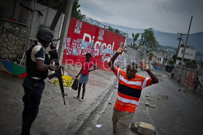 """© Remi OCHLIK/IP3 - Port au Prince on 2010 december 9 - PORT-AU-PRINCE -- Clashes and shooting were reported Thursday in Haiti's capital for a second day as demonstrators staged a march to protest what they said was election fraud in the Nov. 28 presidential elections..The protests broke out Wednesday after election officials announced Tuesday night that two candidates had made it into a runoff: Mirlande Manigat, a former first lady, and Jude CÈlestin, the candidate of current President RenÈ PrÈval's party. Out of the running was Michel """"Sweet Micky'' Martelly, who early results had shown running second. -  Haitian policemen try to remove roadblocks in delmas neighborhood."""