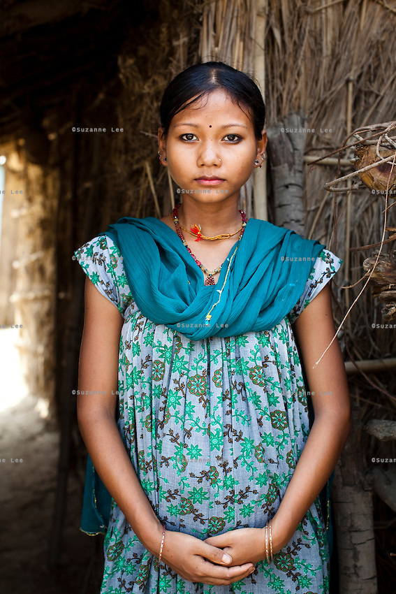 Sita Tharu, 14, is six months pregnant as she poses for a portrait in Bhaishahi village, Bardia, Western Nepal, on 29th June 2012. Sita eloped and married last year at 13 and is now 6 months pregnant. She says she's very afraid of the birth and its possible complications. In Bardia, StC works with the district health office to build the capacity of female community health workers who are on the frontline of health service provision like ante-natal and post-natal care, and working together against child marriage and teenage pregnancy especially in rural areas. Photo by Suzanne Lee for Save The Children UK