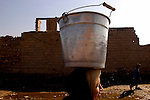 An Iraqi woman carries water back to her home in the village of Shaura on the outskirts of Baghdad. 10,000 liters of water is dropped off every other day by the Red Cross for the village of 6000 people.