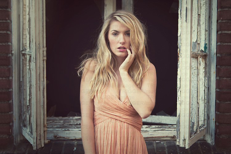 young woman with blonde hair looking straight into the camera and wearing a  vintage dress