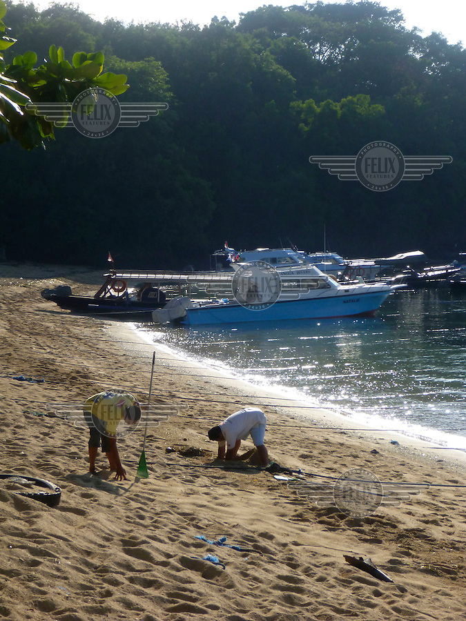 Two worker clean a small strip of beach for garbage, burying some of what they find in the sand, as they prepare to have tourists go on a boat from Padangbai.