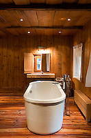 The contemporary free-standing bath strikes a note of contrast in this traditional wood-panelled bathroom