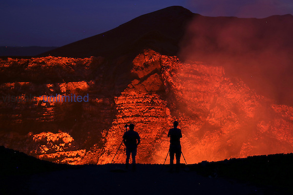 Photographer silhouettes on rim of Santiago Crater overlooking lava lake of Masaya Volcano, Nicaragua.