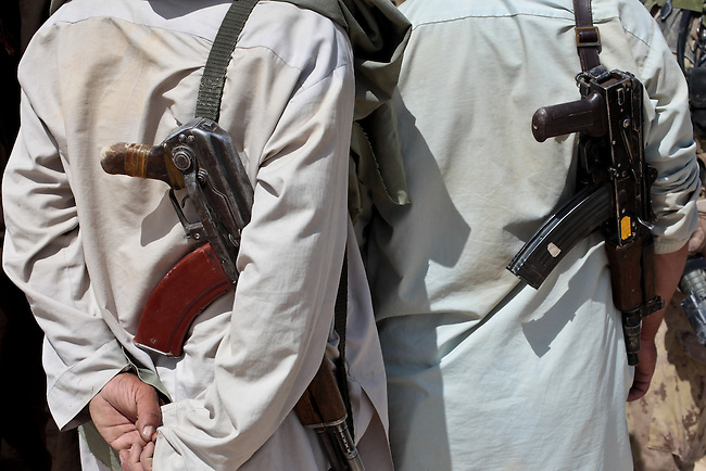 Two armed villagers stand with Kalashnikov rifles slung over their shoulders as the talk with U.S. and Canadian soldiers outside the village of Zormashor in Dand district near Kandahar, Afghanistan. With U.S. and Afghan forces unable to reach many rural areas, they are turning increasingly to Afghan village militias to arm and protect themselves against the Taliban. June 27, 2010. DREW BROWN/STARS AND STRIPES
