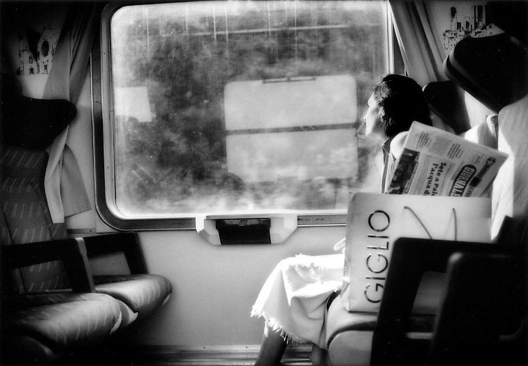 En route to Palermo, Sicily: Woman is bathed by the sun on a train bound for Palermo, Sicily, Italy.