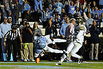 17 October 2015: UNC's Marquise Williams (12) scores a touchdown as Wake Forest's Brad Watson (right) trails the play. The University of North Carolina Tar Heels hosted the Wake Foresst University Demon Deacons at Kenan Memorial Stadium in Chapel Hill, North Carolina in a 2015 NCAA Division I College Football game. UNC won the game 50-14.