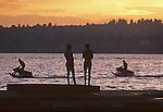 Lake Washington sunset with boys on dock silhouetted with two boys on jet skies Kirkland Washington State USA