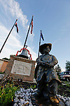 A firefighter statue in a memorial at a firehouse with blue skies and flags in the background in Clifton Heights, Pennsylvania.