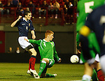 Jamie Murphy scores for Scotland past the challenge of Chris Casement