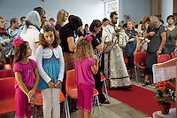 Italy. Lazio region. Guidonia. An orthodox priest, some children, women and men during an orthodox sunday mass. Every single person is a romanian citizen and lives in Italy as an immigrant. Red plastic chairs and carpet. Flower pot. Romanian immigration. Guidonia is a town and comune in the province of Rome. 02.10.2011 © 2011 Didier Ruef