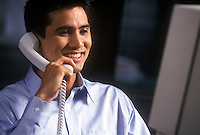 Young speaking on a phone while consulting a computer monitor.