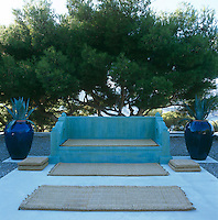 A pair of dark blue urns flanks a Moroccan-style turquoise-painted concrete bench on a concrete patio which floats on a sea of dark grey pebbles in the garden