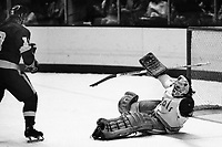 """Los Angles Kings #19 Robert """"Butch"""" Goring scores goal against Seals goalie Gary Simmons. (1975 photo by Ron Riesterer)"""