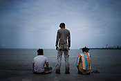 Local Mumbaikars are seen waiting spending time on the sea front in Marine Drive in Mumbai.