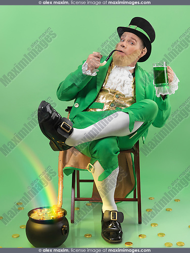 Leprechaun in bright green clothes holding a smoking pipe and a beer mug with a rainbow coming from a pot full of gold. Isolated on white background.